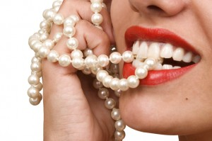 woman smiles showing white teeth and pearly necklace